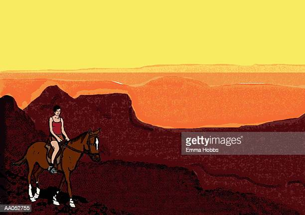 Woman riding horse through mountains at sunset