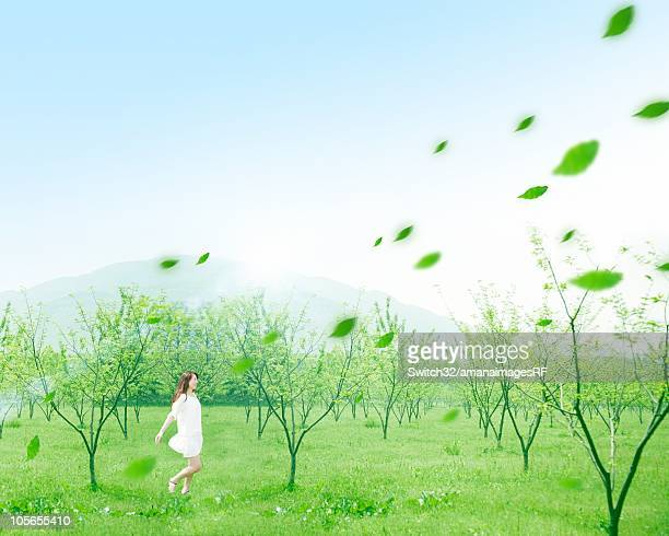 A Woman Running Through a Forest With Digitally Generated Leaves Floating Through the Air