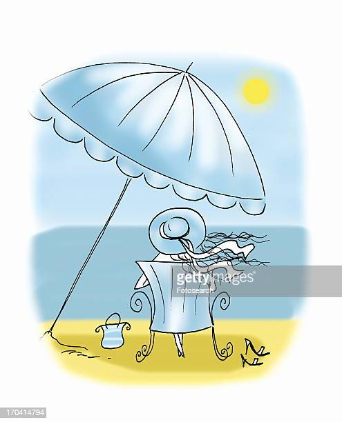 Woman sitting on beach under umbrella