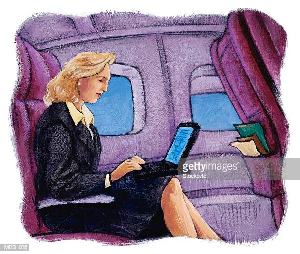 Woman using laptop computer in airplane