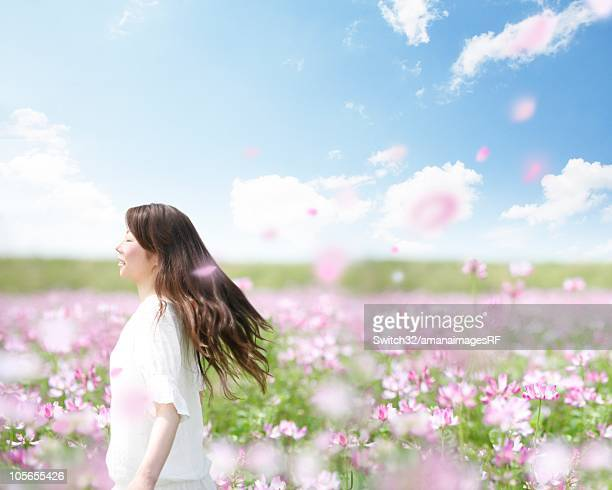 A Woman Walking Happily Through a Field of Pink Flowers and Floating Petals