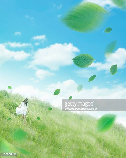 A Woman Walking in a Grassy Field With Digitally Generated Leaves Floating in the Air