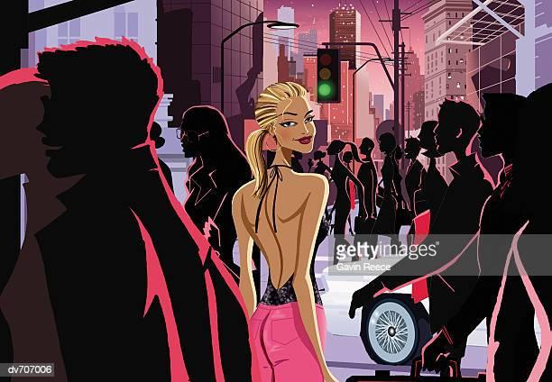 Woman Walking Through a Crowded Urban Street at Night