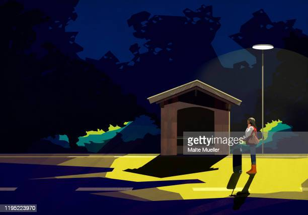 woman with suitcase waiting under street light at dark bus stop - journey stock illustrations