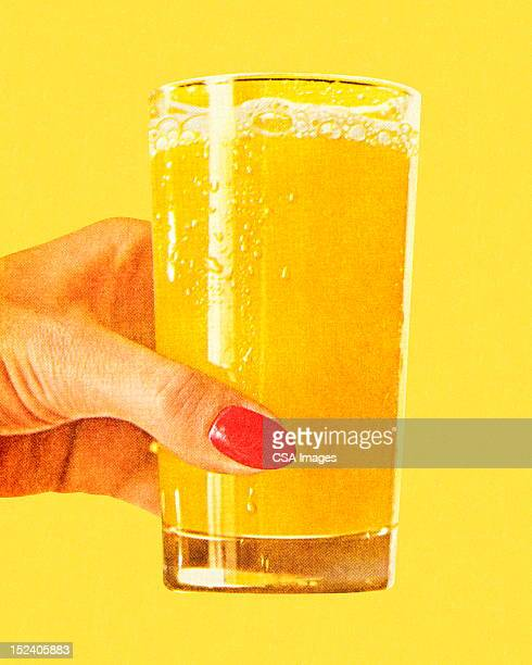 Woman's Hand Holding Glass of Orange Juice