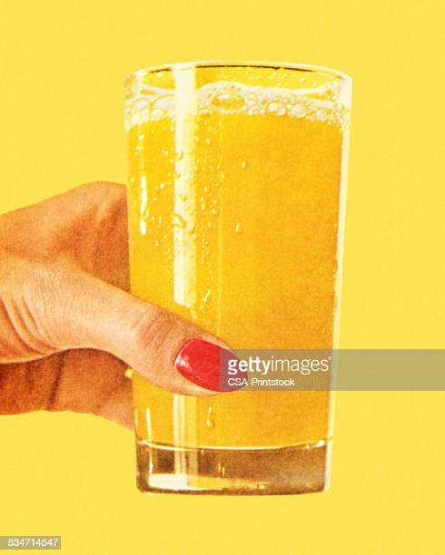 Woman's Hand Holding Glass of Orange Juice