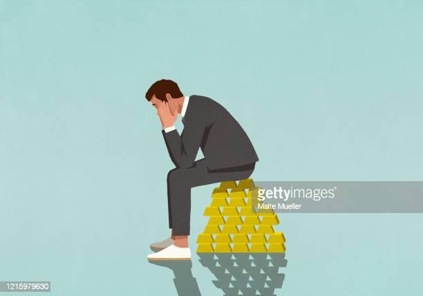 worried male investor sitting on stack of gold bars - 心配する点のイラスト素材/クリップアート素材/マンガ素材/アイコン素材