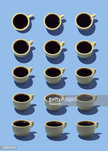 Yellow coffee cups on light blue ground, 3D Rendering