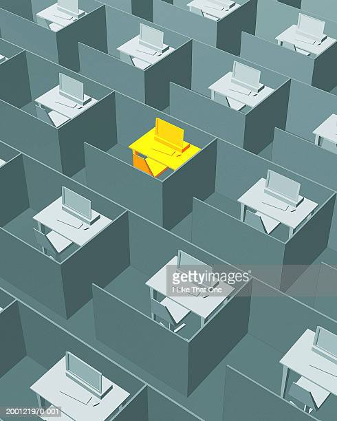 Yellow desk amongst office cubicals containing grey desks