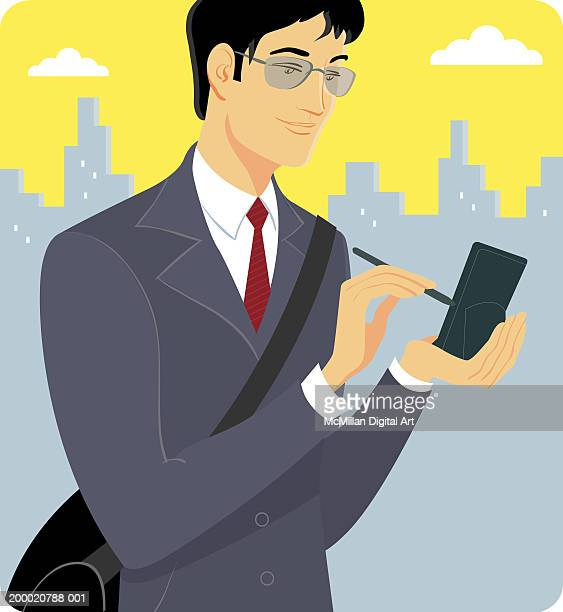 Young businessman working on handheld computer in urban setting