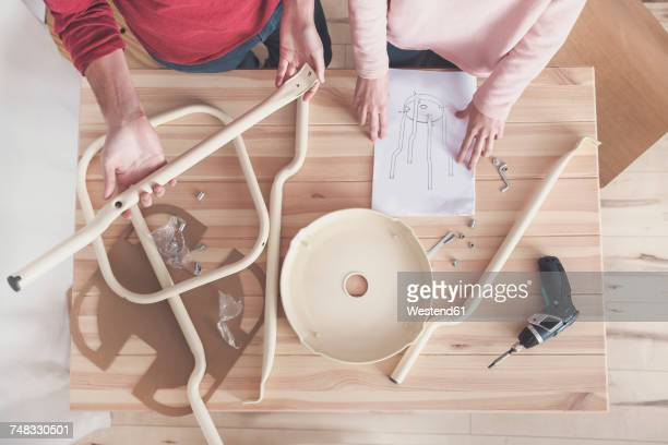Young couple assembling flat-pack stool at home, partial view