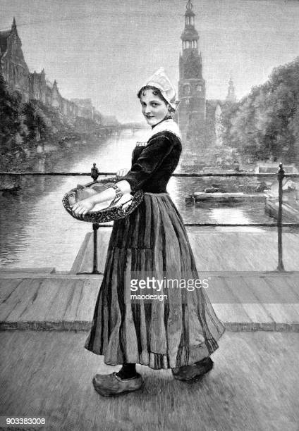Young Dutch girl, wearing a traditional dress and a basket in his hands, stands on a bridge in Amsterdam - 1896