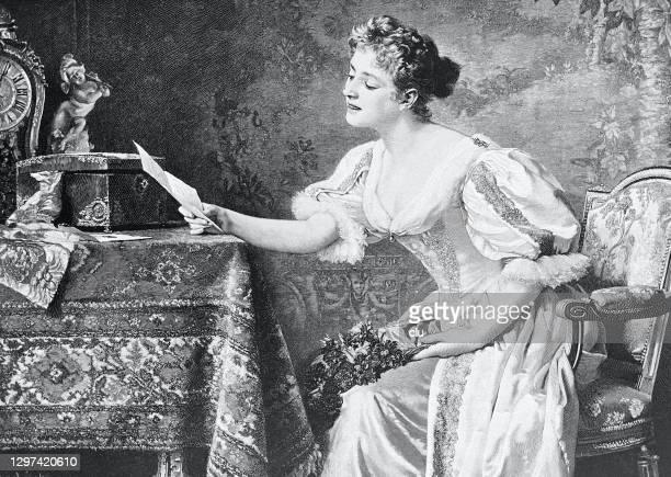 junge weibliche schönheit lesen den liebesbrief am tisch - neunzehntes jahrhundert stock-grafiken, -clipart, -cartoons und -symbole