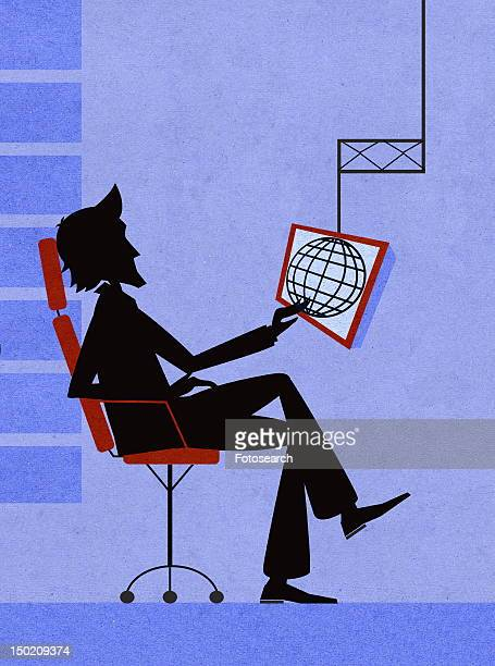 Young man sitting looking at globe on computer screen