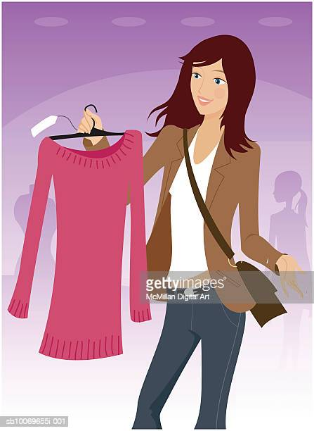 Young woman holding tunic on hanger