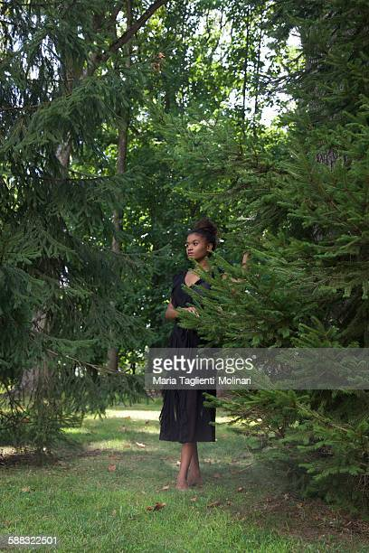 Young woman in green evergreen trees