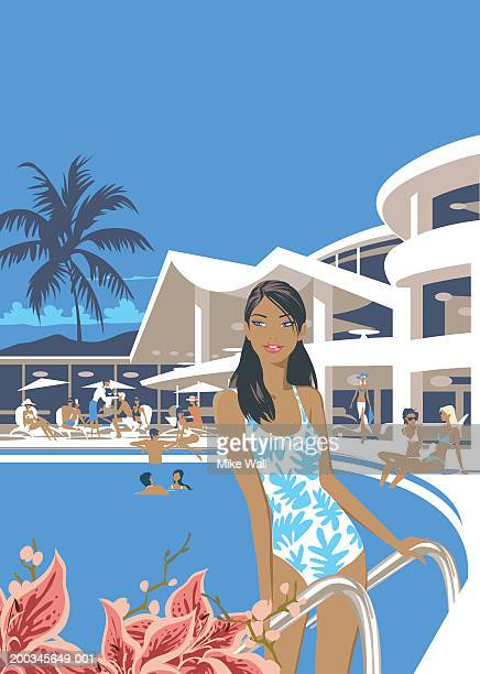 Young woman standing on ladder in resort swimming pool