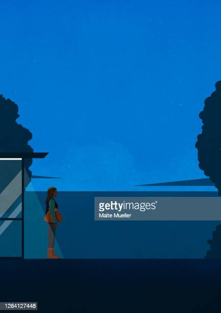 young woman waiting at dark bus stop at night - one young woman only stock illustrations