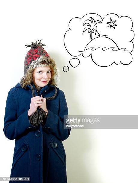 young woman wearing winter coat with tropical island in thought bubble - overcoat stock illustrations