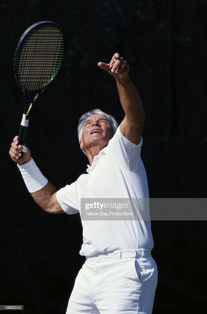 MATURE MAN WITH TENNIS RACKET : Stock Photo