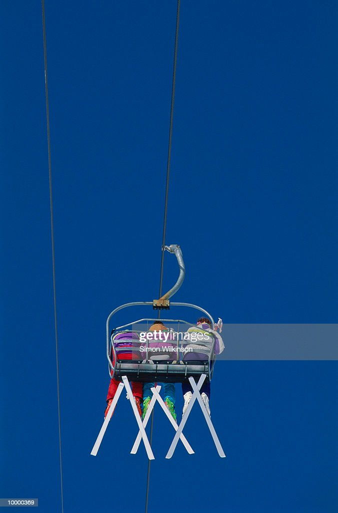 BACKVIEW OF THREE SKIERS ON CHAIR LIFT : Stock Photo