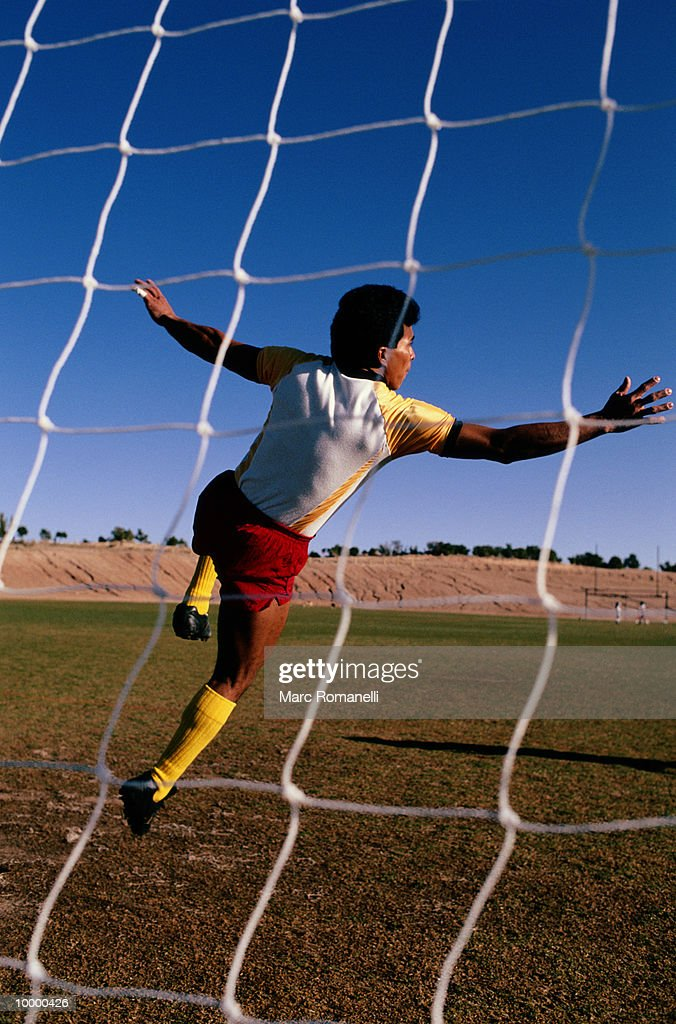 SOCCER PLAYER VIEWED THRU NET : Stock Photo
