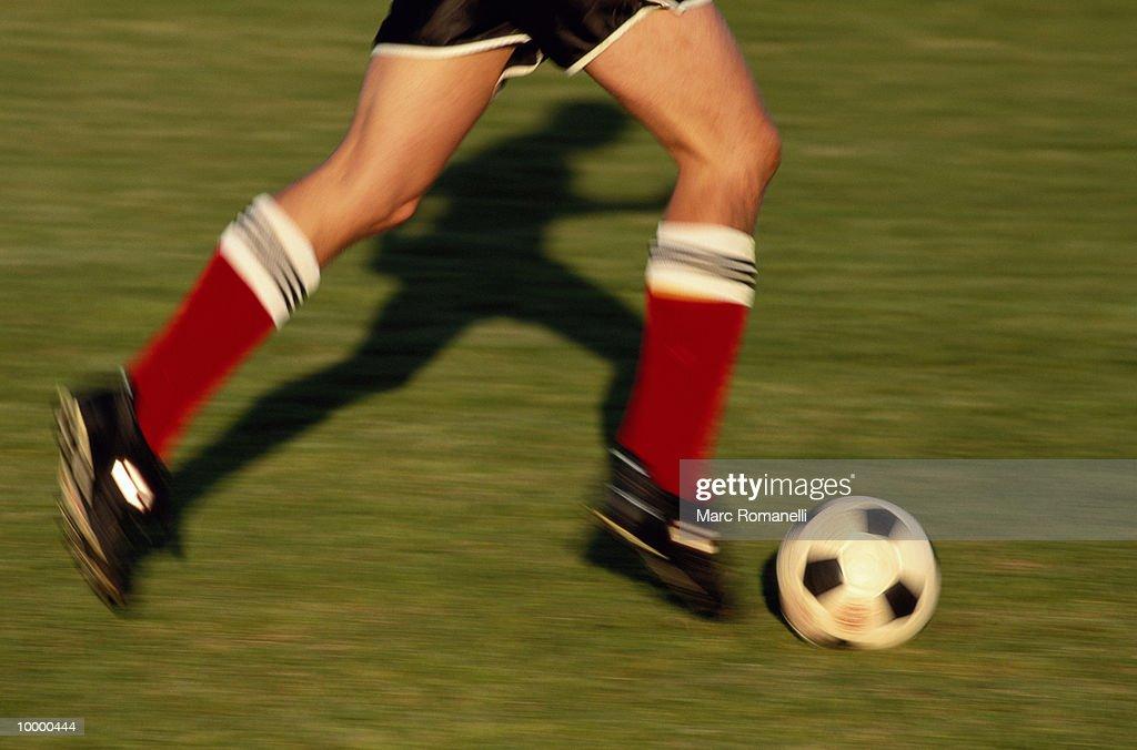 SOCCER PLAYER'S LEGS DRIBBLING BALL : Stock Photo