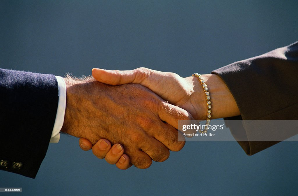 BUSINESSMAN'S & WOMAN'S HANDSHAKE : Stock-Foto