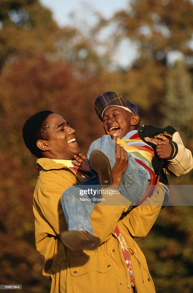 BLACK FATHER PLAYING WITH YOUNG SON OUTDOORS : Stock Photo