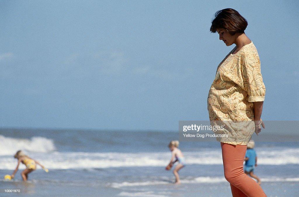 PREGNANT WOMAN WALKING ON BEACH : ストックフォト