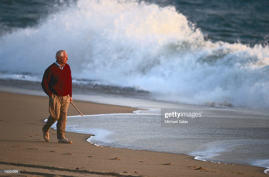 MATURE MAN WALKING ON BEACH : Stock Photo