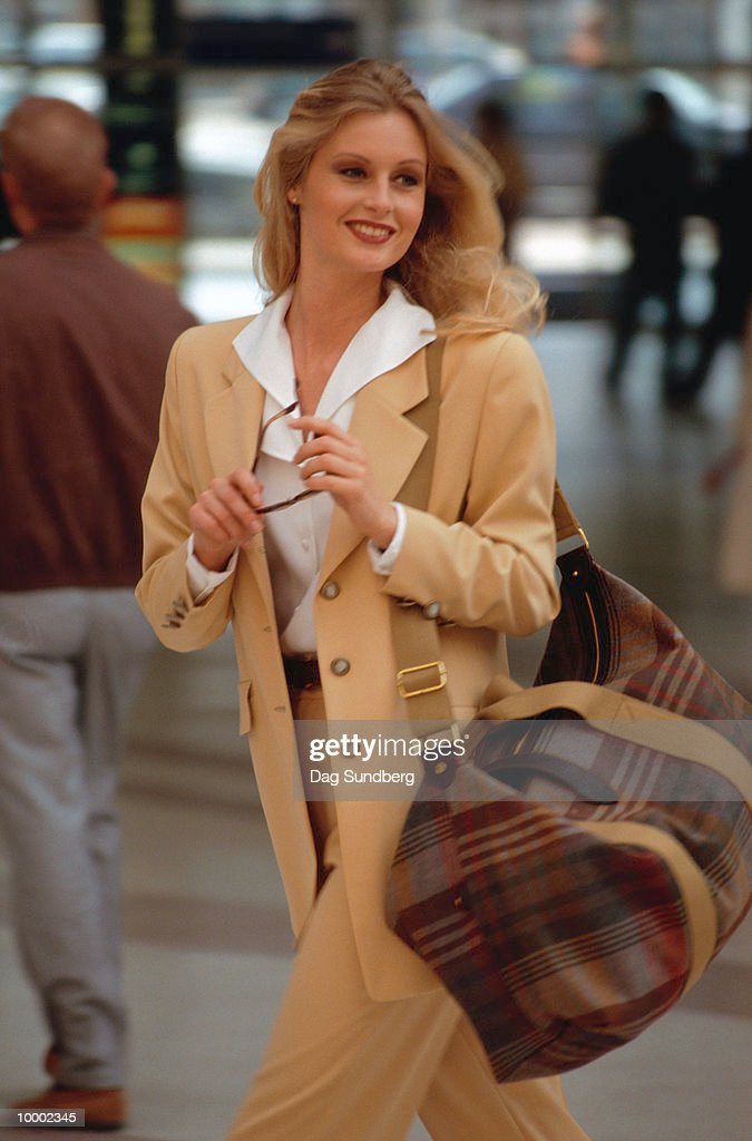 BLONDE WOMAN WALKING OUTDOORS WITH BAG : Foto de stock