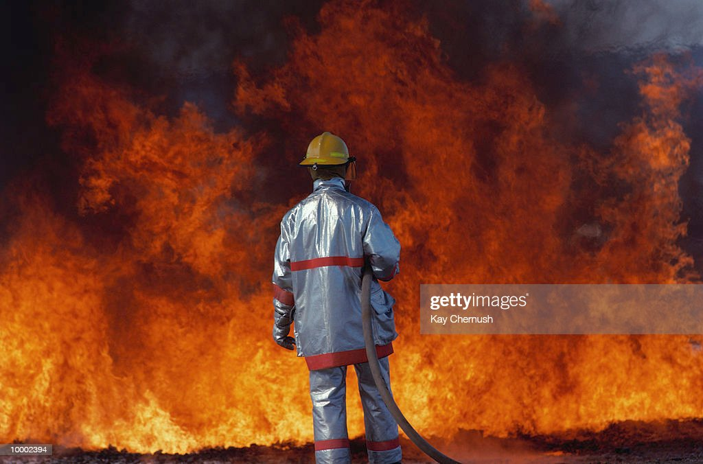 BACK VIEW OF A FIREFIGHTER WITH HOSE & FIRE : Stock Photo