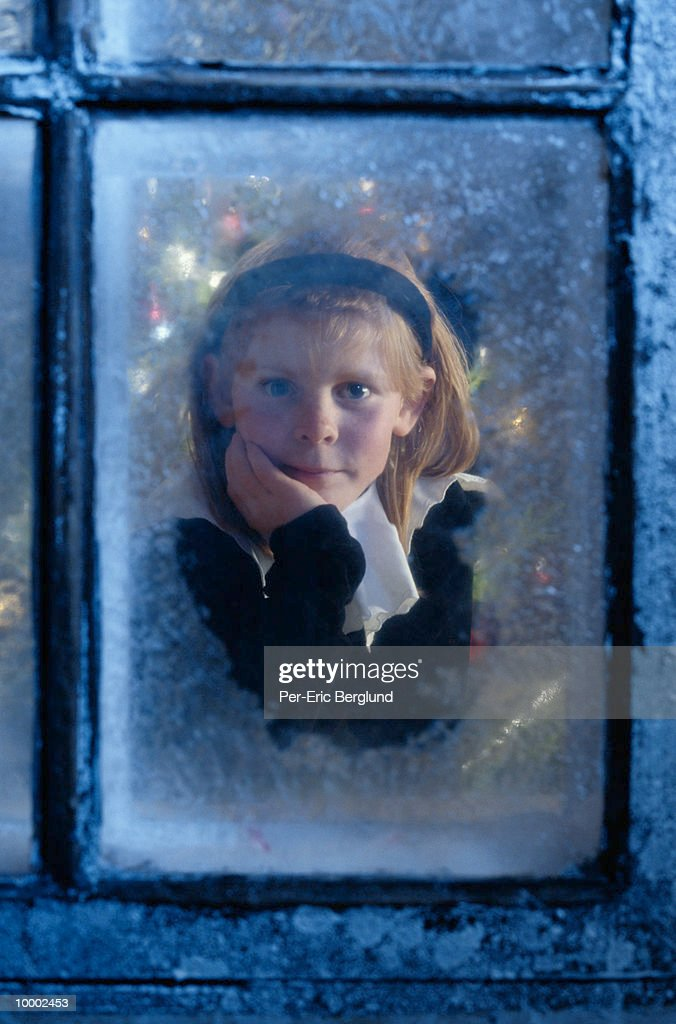 GIRL WATCHING FOR SANTA FROM ICY WINDOW : Stockfoto