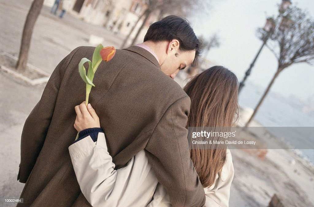 MAN & WOMAN WITH TULIP WALKING NEAR WATER : Stock Photo