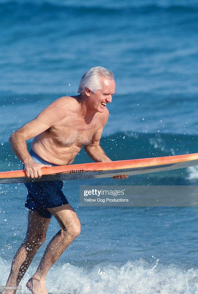 MATURE MAN WITH SURFBOARD IN OCEAN : Stock Photo