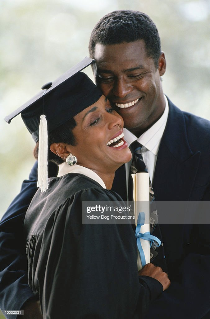BLACK COUPLE WITH WOMAN GRADUATING : Stock Photo