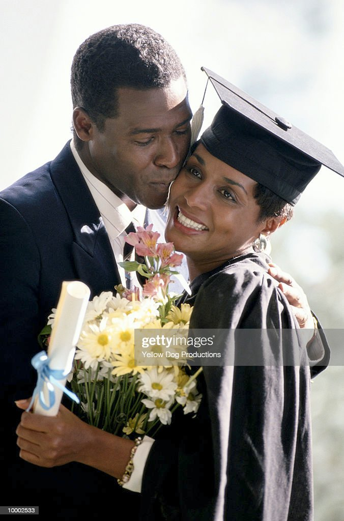 BLACK COUPLE AT WOMAN'S GRADUATION : Bildbanksbilder
