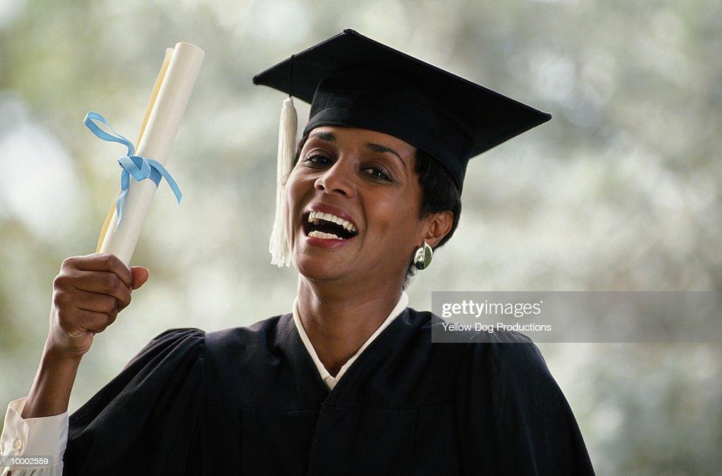 BLACK FEMALE GRADUATE HOLDING DIPLOMA : Bildbanksbilder