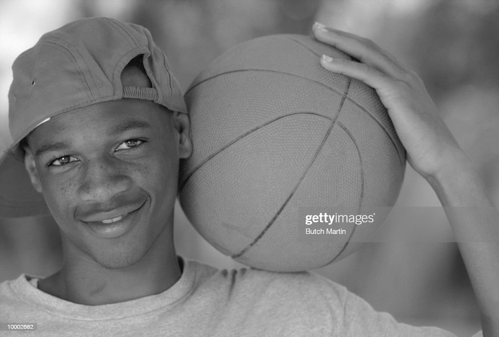 BLACK TEENAGE MALE WITH BASKETBALL IN BLACK AND WHITE : Stock Photo