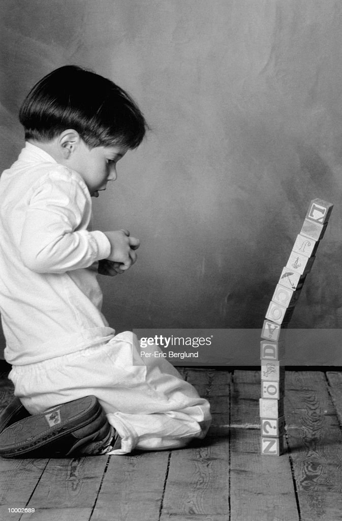 YOUNG BOY WITH STACKED BLOCKS IN BLACK AND WHITE : Foto de stock