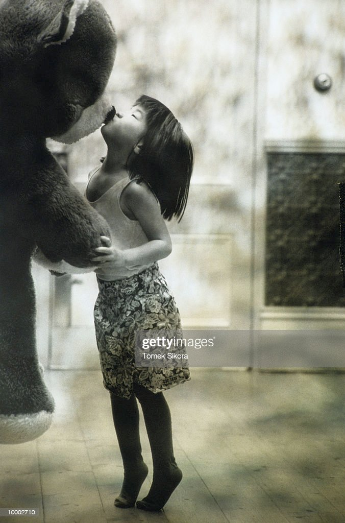 ASIAN GIRL KISSING BIG STUFFED BEAR IN BLACK AND WHITE : Stock Photo