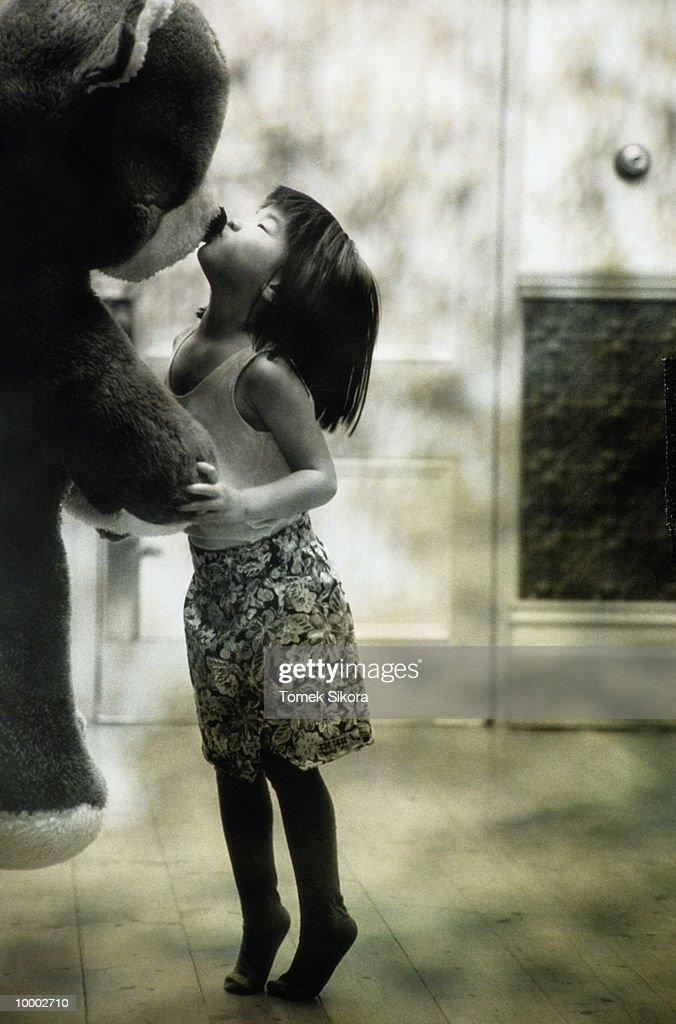 ASIAN GIRL KISSING BIG STUFFED BEAR IN BLACK AND WHITE : Bildbanksbilder
