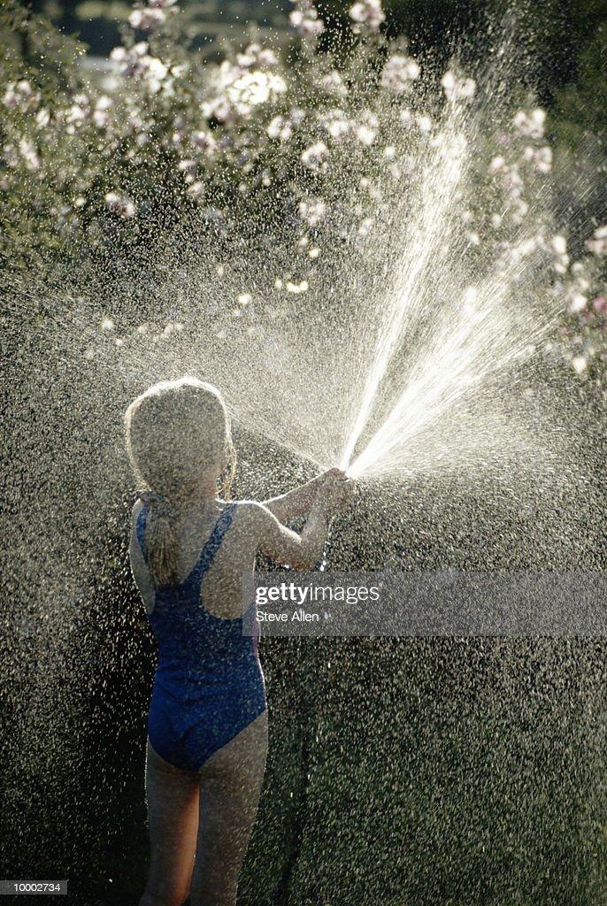 GIRL SPRAYING WATER HOSE : Stock Photo