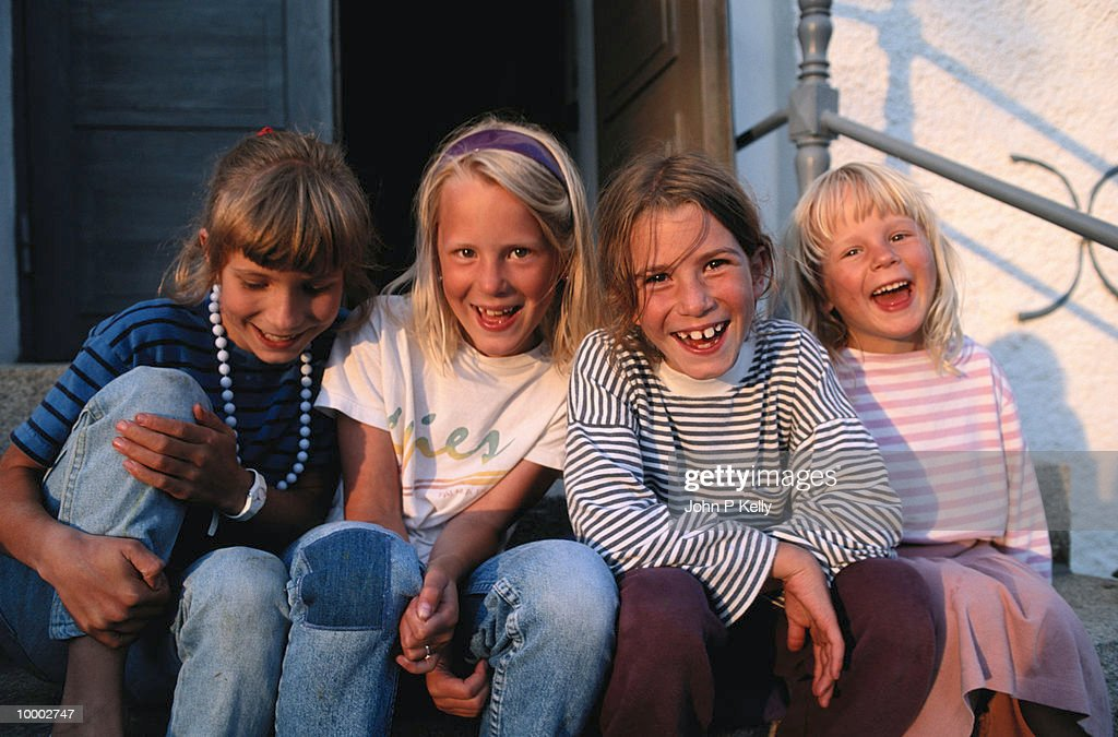 YOUNG GIRLS LAUGHING OUTDOORS IN SWEDEN : Stock Photo
