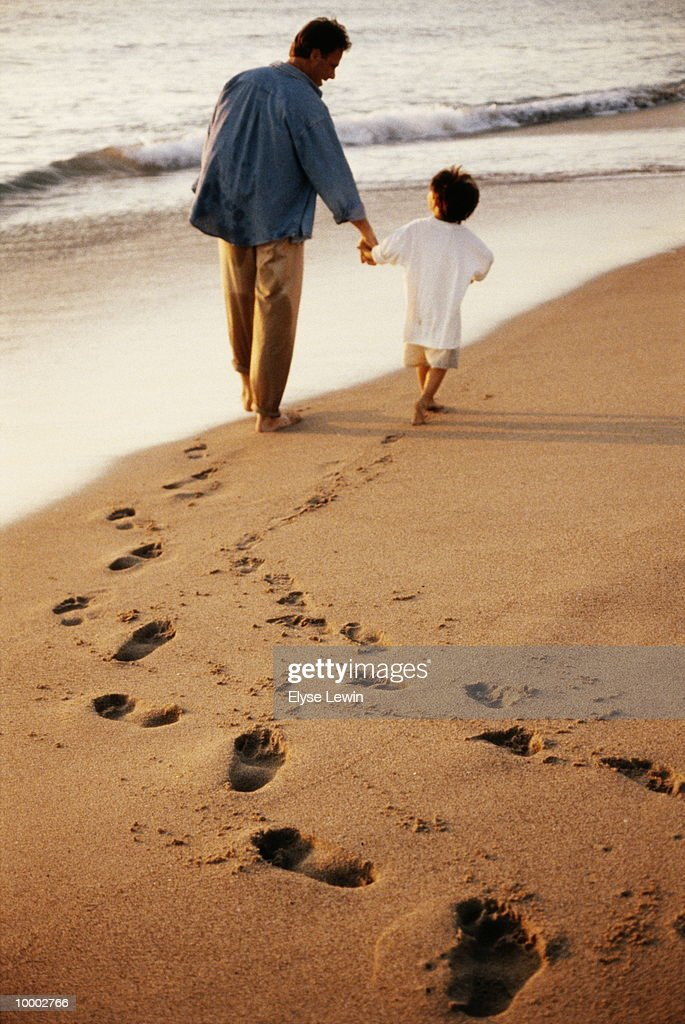 DAD & BOY WALKING ON BEACH WITH FOOTPRINTS : ストックフォト
