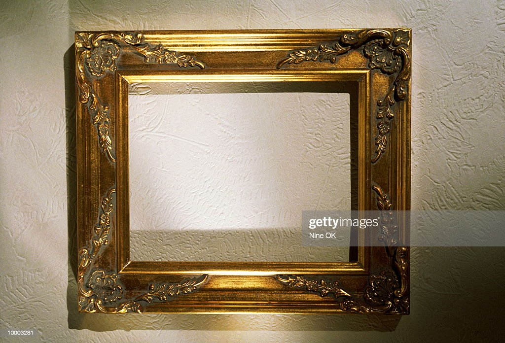 EMPTY GOLD PICTURE FRAME ON A WALL : Stock-Foto