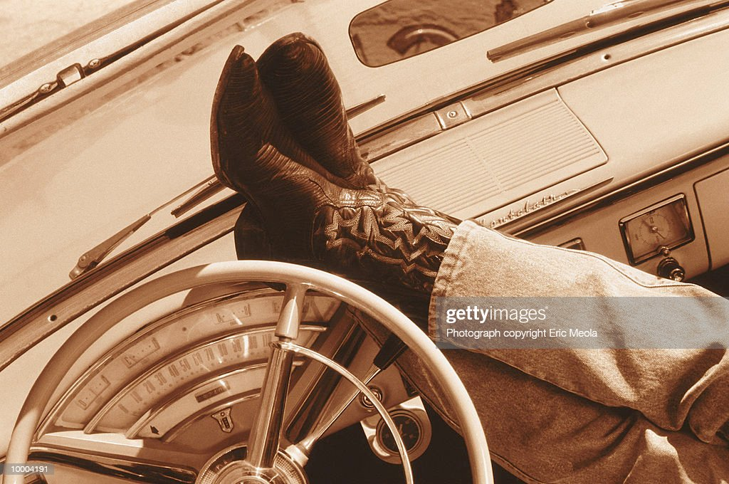 FEET IN WESTERN BOOTS ON DASHBOARD IN SEPIA : Stock Photo