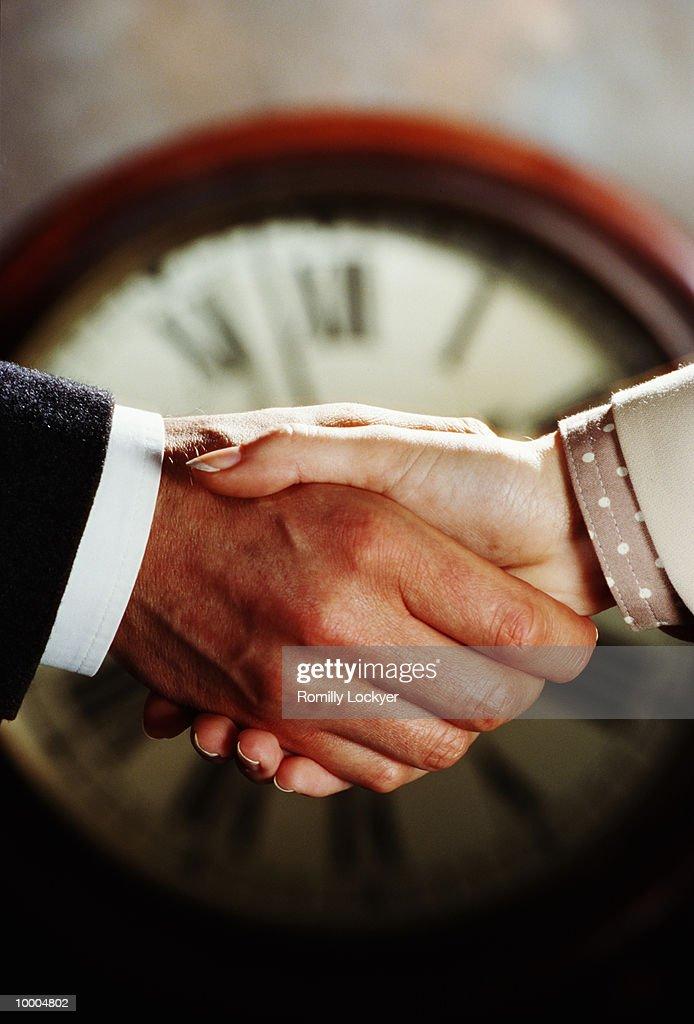 CLOCK BEHIND BUSINESS COUPLE'S HANDSHAKE : Stockfoto