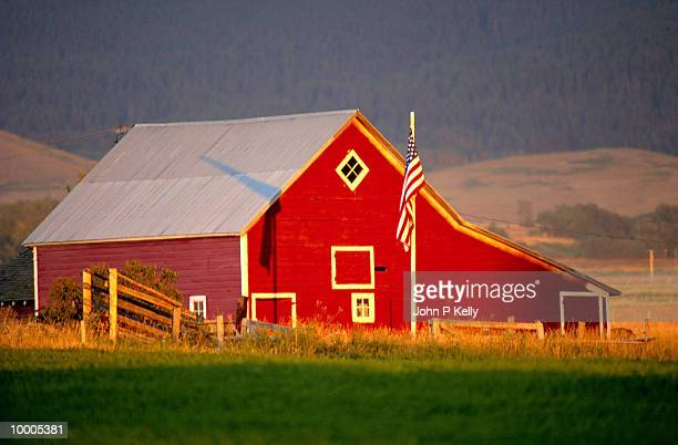 RED BARN ON FARM WITH UNITED STATES FLAG IN MONTANA